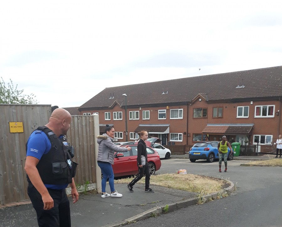 An officer and residents outside in the street at a social distance